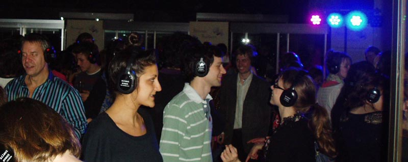 a group of people enjoying themselves at a silent disco, all wearing wireless headphones